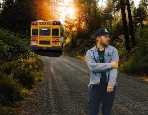 Young male adult stands, looking confused, in front of a bus driving off into the distance on a rural dirt road.