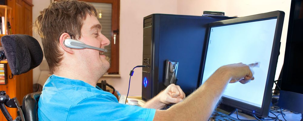 Man uses aassistive technology to complete his work tasks.