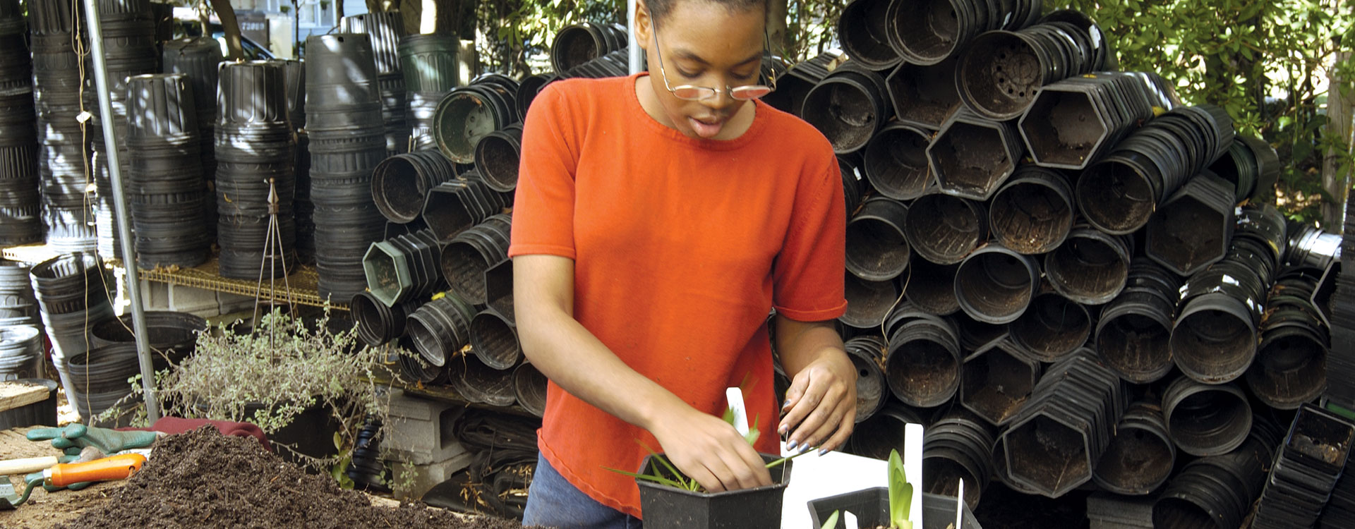 An image of a young woman learning gardening skills through potting plants. The background shows a wall of plastic plant pots.