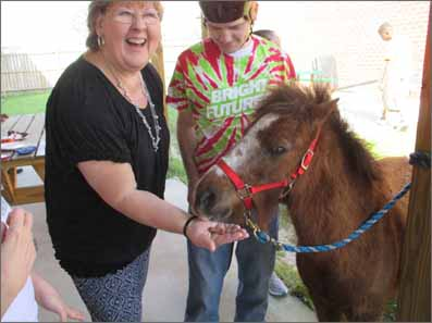 A woman helps a young man with intellectual and/or developmental disabilities feed a miniature horse as a therapeutic activity.
